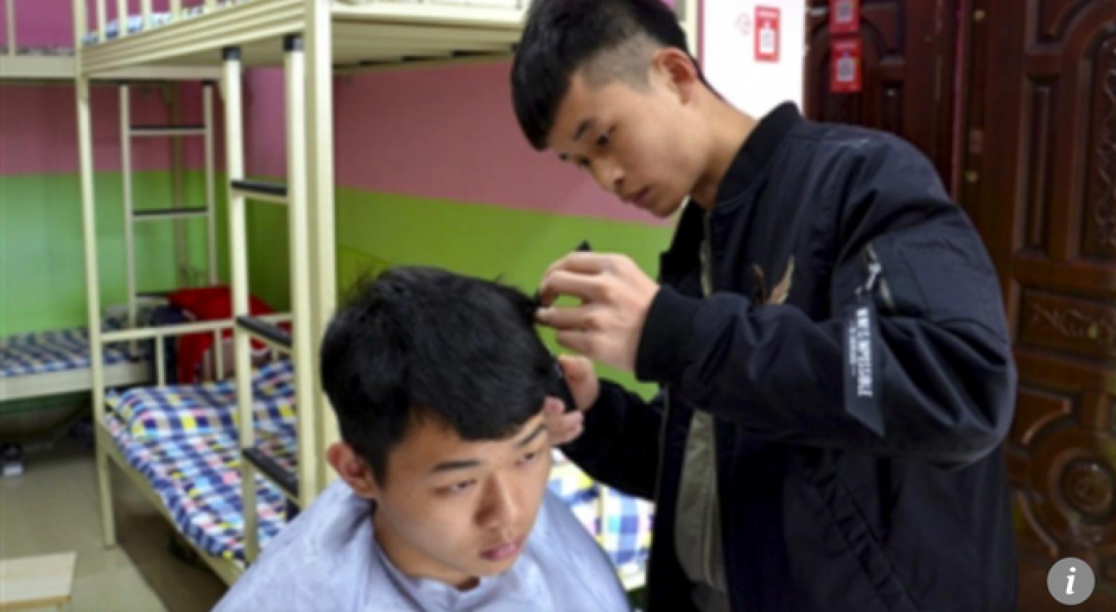 Đinh Duy Kiệt đang cắt tóc cho 1 vị khách hàng tại ký túc xá của trường (Ảnh: Sina)